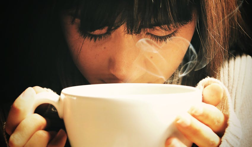 holding and drinking hot beverage